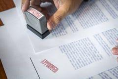 De handen van zakenman stempelen op document document om de overeenkomst van het handelsinvesteringencontract goed te keuren stock fotografie