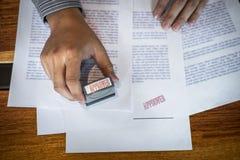 De handen van zakenman stempelen op document document om de overeenkomst van het handelsinvesteringencontract goed te keuren stock foto's