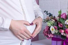 De handen van de zwangere vrouw op haar buik die een hart, boeket maken van pu royalty-vrije stock afbeelding
