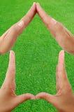 De handen vormen de vorm van een huis Stock Fotografie
