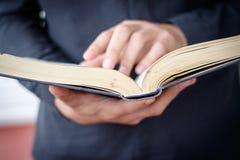 De handen vouwden in gebed op een Heilige Bijbel in kerkconcept voor geloof, spirtuality en godsdienst stock foto's