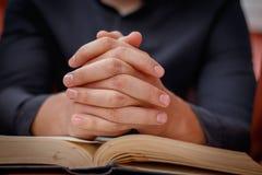 De handen vouwden in gebed op een Heilige Bijbel in kerkconcept voor geloof, spirtuality en godsdienst royalty-vrije stock foto's