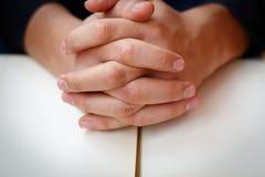 De handen vouwden in gebed op een Heilige Bijbel in kerkconcept voor geloof, spirtuality en godsdienst stock fotografie