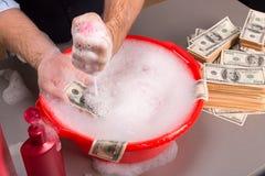 De handen wassen dollarsbankbiljetten in schuim Stock Foto's