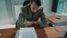 De handen zetten grote stapel van administratie op lijst van vermoeide beambte in plaidjasje stock video
