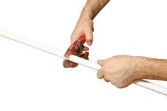 De handenarbeider snijdt een stuk polypropyleenpijpen af Geïsoleerd4 o Royalty-vrije Stock Foto's