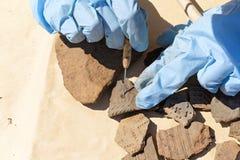 De handenarcheoloog maakte met een schraper van klei van een fragment van een oud schip schoon royalty-vrije stock foto