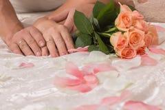 De de handenbruid en bruidegom die een mooi kleurrijk bloeiend boeket van rozen houden, liggen op het bed stock foto