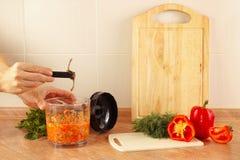 De handenchef-koks verwijderen messenmixer na het koken van plantaardige mengeling Stock Foto's