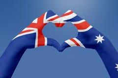De handenvlag van Australië, vormt een hart Concept het symbool van het land, op blauwe hemel Stock Afbeeldingen