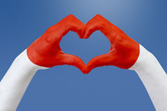 De handenvlag van Monaco, vormt een hart Concept het symbool van het land, op blauwe hemel Stock Fotografie