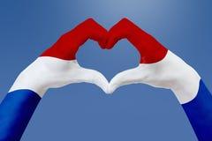 De handenvlag van Nederland, vormt een hart Concept het symbool van het land, op blauwe hemel Stock Afbeelding