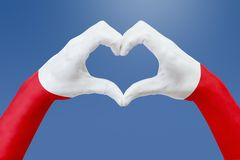 De handenvlag van Polen, vormt een hart Concept het symbool van het land, op blauwe hemel Royalty-vrije Stock Foto