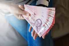 De handenvrouw toont en tellend Thais geld Royalty-vrije Stock Afbeeldingen