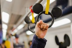 De handgreep van de vrouwenholding in Disney-Lijn MTR binnen van Zonnige baai aan Hong Kong Disneyland-toevlucht, oriëntatiepunt  stock foto's