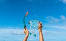 De handholding snorkelt beschermende brillen (masker voor het duiken) tegen strand en hemel het zand Royalty-vrije Stock Fotografie