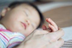 De handholding van de moeder van weinig jonge leuke Aziatische babyslaap op het bed Sluit omhoog mening bij babyvingers royalty-vrije stock afbeeldingen