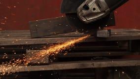 De handmachine voor de werken om metaal te snijden Vonkenvlieg aan de partijen stock footage