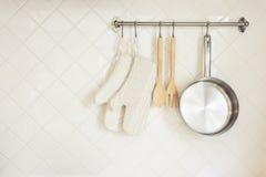 De Handschoen en Pan Wooden Spoon van het keukenwerktuig op Tegelsmuur Royalty-vrije Stock Foto's