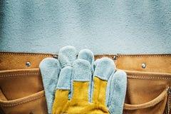 De handschoenen van de de riemveiligheid van het leerhulpmiddel op concrete achtergrond Stock Afbeeldingen
