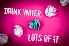 De handschrifttekst drinkt Water Veel het Concept die drinkend vloeistoffen om ons lichaam in grote status Lichtrose vloer te hou stock afbeelding