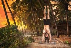 De handstand van de yoga stelt bij zonsondergang Stock Foto's