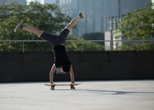 de handstand van de vrouwenpraktijk op skateboad bij stad Royalty-vrije Stock Foto's