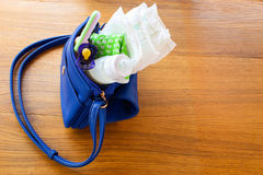 De handtas van vrouwen met punten aan zorg voor het kind: fles melk, beschikbare luiers, rammelaar, fopspeen en babykleren Stock Afbeeldingen