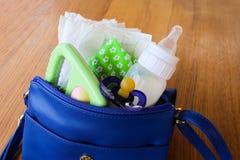 De handtas van vrouwen met punten aan zorg voor het kind: fles melk, beschikbare luiers, rammelaar, fopspeen en babykleren Stock Foto's