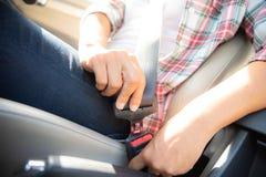 De handzitting van de close-upvrouw binnen auto het vastmaken zetelbeltu stock foto's