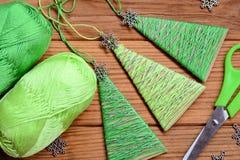 De hangende Kerstbomen worden gemaakt van karton, katoenen garen en met metaalsneeuwvlokken verfraaid Eenvoudige en goedkope Kers royalty-vrije stock fotografie