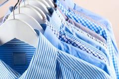 De hangers van de doek met overhemden Mensen` s kleren Stock Foto's
