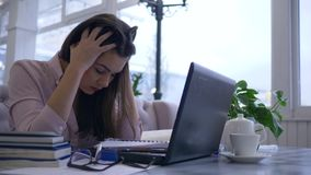 De harde studie, het vermoeide studentenmeisje voorbereidingen treffen voor examens gebruikt laptop computer om met onlinetrainin stock videobeelden