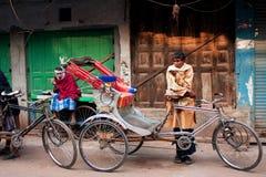 De harde werkende riksja wacht op de passagiers met zijn uitstekende fietscabine op de straat Royalty-vrije Stock Afbeelding