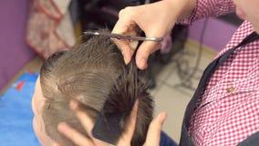 De haren van het kappermalen met schaar op het hoofd van de jongen Hoogste mening, de handenclose-up van de stilist stock videobeelden