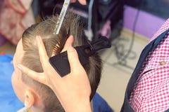 De haren van het kappermalen met schaar op het hoofd van de jongen Hoogste mening, de handenclose-up van de stilist royalty-vrije stock afbeelding