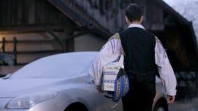 De harmonikamusicus komt aan zijn auto met ijzige vensters aan stock footage