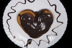 De hart-vormige behandelde broodjeschocolade, ligt op een witte plaat stock fotografie