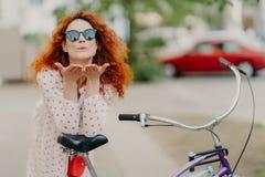 De hartelijke roodharigevrouw verzendt luchtkus naar minnaar op straat, houdt palmen dichtbij mond, draagt om schaduwen, kleding, stock fotografie
