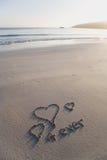 De harten van de liefde en voor altijd geschreven op een oorspronkelijke beac Stock Fotografie