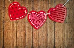 De Harten van drie Valentine op een Houten Plankachtergrond Stock Fotografie