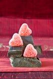 De Harten van het suikergoed op een Stapel van de Donkere Stukken van de Chocolade Stock Foto's