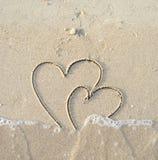 De harten van ?onnected die op nat zand worden getrokken Stock Foto