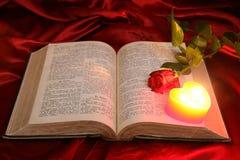 De hartkaars op open Bijbel en rood nam toe Stock Foto's