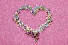 De hartvorm van lovertjes, de flikkering en de confettien voor manicure ontwerpen op heldere roze achtergrond stock afbeeldingen