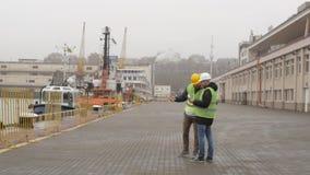 De havenarbeiders in helmen bekijken documenten Zeehaven