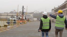 De havenarbeiders in helmen gaan naar de haven en de bespreking