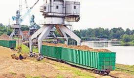 De havenkraan maakt lading van houten spaanders in de goederenwagonnen van de trein, lading stock afbeelding