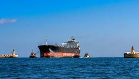 De havensleepboten die een groot schip van de olieproductentanker bijstaan gaan de haven in stock foto's
