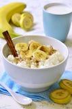 De havermoutpap van de melkrijst met banaan, kaneel en honing Royalty-vrije Stock Afbeeldingen